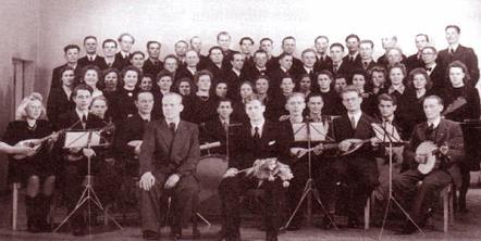 Kuvassa Kuoro ja Soitinyhtye. Mauno Saksanen istuu eturivissä kukkia sylissään